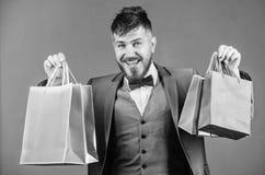 Mężczyzny brodaty elegancki biznesmen niesie torby na zakupy na popielatym tle Cieszy się robiący zakupy zyskowne transakcje czar zdjęcia stock