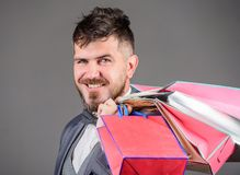Mężczyzny brodaty elegancki biznesmen niesie torby na zakupy na popielatym tle Robi robić zakupy radosnego Elity butik enjoy obrazy stock