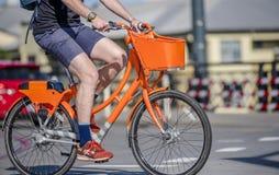 Mężczyzny cyklista jedzie społecznie dzierżawiącego pomarańczowego bicykl przy rozdrożem na miasto ulicie zdjęcia stock