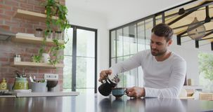 Mężczyzny dolewania kawa w filiżance przy łomotać stół w wygodnym domu 4k zbiory wideo