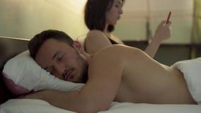 Mężczyzny dosypianie w łóżku w przedpolu podczas gdy jego gniewna niezadowolona żona siedzi blisko patrzeć on z złością i zdjęcie wideo