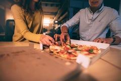 Mężczyzny i kobiety łasowania pizza w biurze przy nocą zdjęcie royalty free