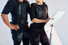 M??czyzny i kobiety cia?o jest ubranym kostiumy dla electro mi??nia pobudzenia EMS obrazy royalty free