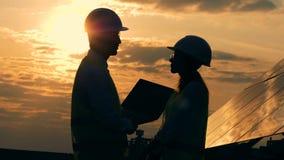 Mężczyzny i kobiety pracownicy budowlani opowiadają na zmierzchu tle, boczny widok zbiory