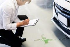 Mężczyzny inspektorskiego przecieku parowozowy olej z białym samochodem w garażu sali wystawowej usługi samochód dla automobilowe zdjęcia stock