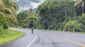 Mężczyzny jeździecki bicykl przez lasu tropikalnego obrazy stock
