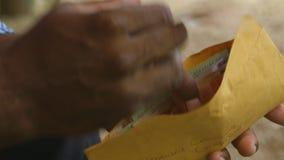Mężczyzny kładzenia pieniądze w kopercie zbiory