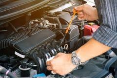 Mężczyzny lub auto mechanika pracownik wręcza sprawdzać samochodowego parowozowego olej utrzymanie i obraz stock