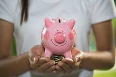 Mężczyzny mienia menchii prosiątka bank Oprócz pieniądze i pojęcia, pieniężnej inwestycji, pieniężnego lub oszczędzania, zdjęcie stock