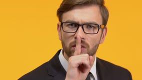 Mężczyzny mienia palec blisko jego warg pokazuje ciszę podpisuje, ściśle tajny dochodzenie zbiory