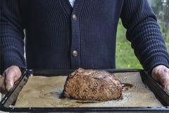Mężczyzny mienie piec na grillu pieczoną wołowinę na ciemnej desce obraz stock