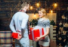 Mężczyzny modniś daje prezentowi dziewczyn bożych narodzeń dekoracji tło Niespodzianka dla sympatii bo?ego narodzenia nowy szcz?? zdjęcie royalty free