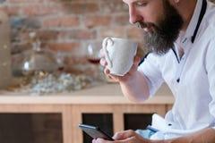 Mężczyzny napoju smartphone wiadomości ewidencyjny surfing fotografia stock