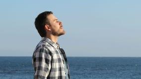 Mężczyzny oddychania relaksujący świeże powietrze na plaży zbiory wideo