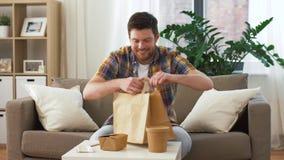 Mężczyzny odpakowanie i łasowania takeaway jedzenie w domu zbiory