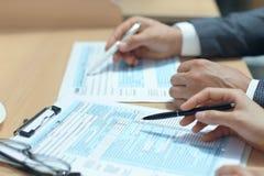 Mężczyzny plombowanie w U S Indywidualny podatku dochodowego powrót, opodatkowywa 1040 przy stołem obraz stock