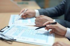 Mężczyzny plombowanie w U S Indywidualny podatku dochodowego powrót, opodatkowywa 1040 przy stołem zdjęcia stock
