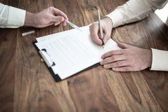 Mężczyzny podpisywania kontrakt przy drewnianym biurkiem z inną osobą wskazuje przy dokumentem obrazy stock