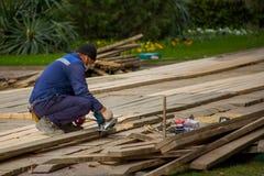 Mężczyzny pracownik w błękitnych prac ubraniach obchodzi się drewniane deski z szlifierską maszyną na tle zieleni krzaki i gazon fotografia royalty free