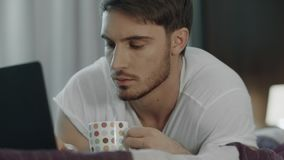 Mężczyzny pracujący laptop z filiżanką w łóżku Męska blogger praca online zbiory