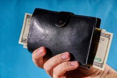 Mężczyzny ręka trzyma portfel z dolarami na błękitnym tle zdjęcie royalty free