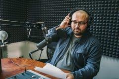 Mężczyzny radia gospodarz, representer lub dziennikarz czytamy wiadomość od papierowej listy w ręce pracowniany mikrofonu obsiada fotografia royalty free
