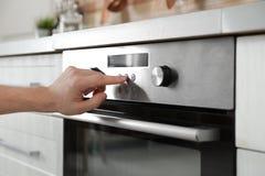 Mężczyzny regulacyjny kulinarny tryb na piekarnika panelu w kuchni, obrazy stock