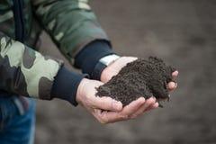 Mężczyzny rolnik lub agronom trzymamy ziemię w jego ręk pokazywać obrazy royalty free