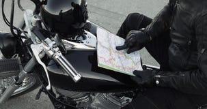 Mężczyzny rowerzysta wybiera trasę na mapy obsiadaniu na jego rowerze, wręcza zbliżenie zbiory