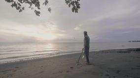 Mężczyzny skarbu myśliwy z wykrywacz metalu pracuje na oceanu piaska plaży przy zmierzchem zbiory wideo