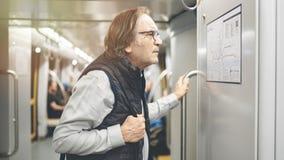 Mężczyzny spojrzenie przy mapą w metro pociągu obraz stock