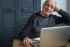 Mężczyzny starszy spojrzenia przy laptopu ekranem, zegarki film w domu, selekcyjna ostrość zdjęcia stock
