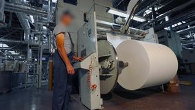 Mężczyzny stojaki w fabryce dla produkcji tapeta Mężczyzna przy fabryką kontroluje maszynę zbiory