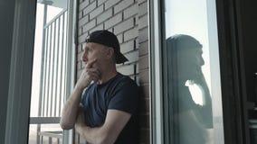 Mężczyzny w średnim wieku stojaki na werandzie i myśleć o jego problemach zdjęcie wideo