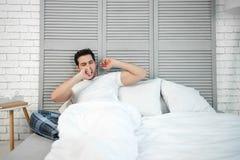 Mężczyzny ziewanie w łóżku fotografia royalty free