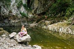 Męcząca i dokuczająca mała dziewczynka odpoczywa na dużej skale zdjęcie stock