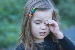 Męcząca lub zanudzająca mała dziewczynka wyciera jej oko zdjęcia stock