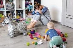 Męczący codzienny gospodarstwo domowe matki obsiadanie na podłodze z rękami na twarzy Dzieciak bawić się w upaćkanym pokoju Scate obraz royalty free