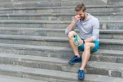 Męczący po trenować na świeżym powietrzu Pobyt nawadniający i zdrowy Macho z bidonem siedzi na krokach, kopii przestrzeń pragnien zdjęcie stock