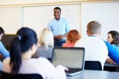 Męscy adiunkta nauczania studenci uniwersytetu W sala lekcyjnej Obrazy Royalty Free