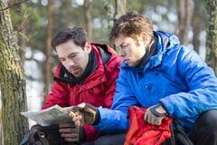 Męscy backpackers czyta mapę w lesie Obrazy Stock