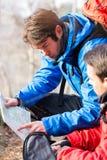 Męscy backpackers czyta mapę w lesie Fotografia Stock