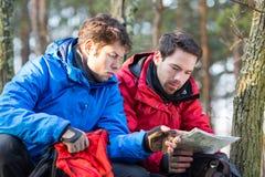 Męscy backpackers czyta mapę w lesie Zdjęcia Stock