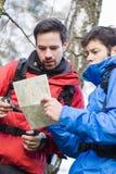 Męscy backpackers czyta mapę w lesie wpólnie Obraz Royalty Free