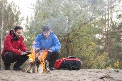 Męscy backpackers grże ręki przy ogniskiem w lesie Fotografia Royalty Free