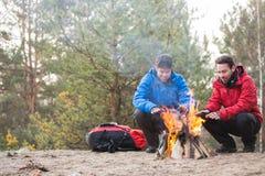 Męscy backpackers grże ręki przy ogniskiem w lesie Obrazy Royalty Free