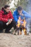 Męscy backpackers ma kawę przy ogniskiem w lesie Obraz Stock