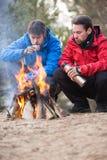 Męscy backpackers ma kawę przy ogniskiem w lesie Zdjęcia Stock
