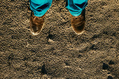 Męscy buty na textured piaska kontrasta błękita spodniach Zdjęcia Royalty Free