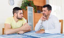 Męscy dorosli dyskutuje o coś Obrazy Royalty Free